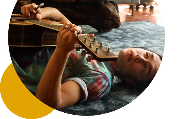 Man lying on the ground holding a guitar and vape pen, looking up, composing his next track.