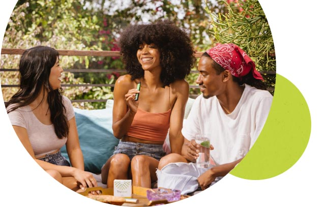 Two smiling women and a man sitting on a patio with a Trulieve product on a table. One of the women holding a vape pen.