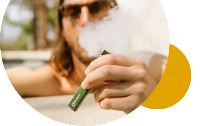 Man in a pool wearing sunglasses exhaling smoke while holding Trulieve vape pen.