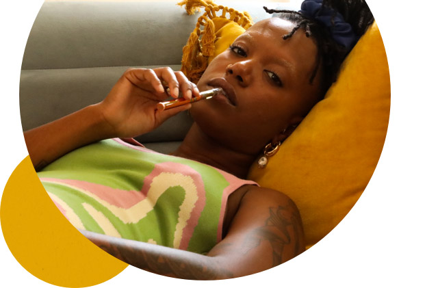 Woman with heavy-eyed face lying on the couch with a vape pen in her mouth.