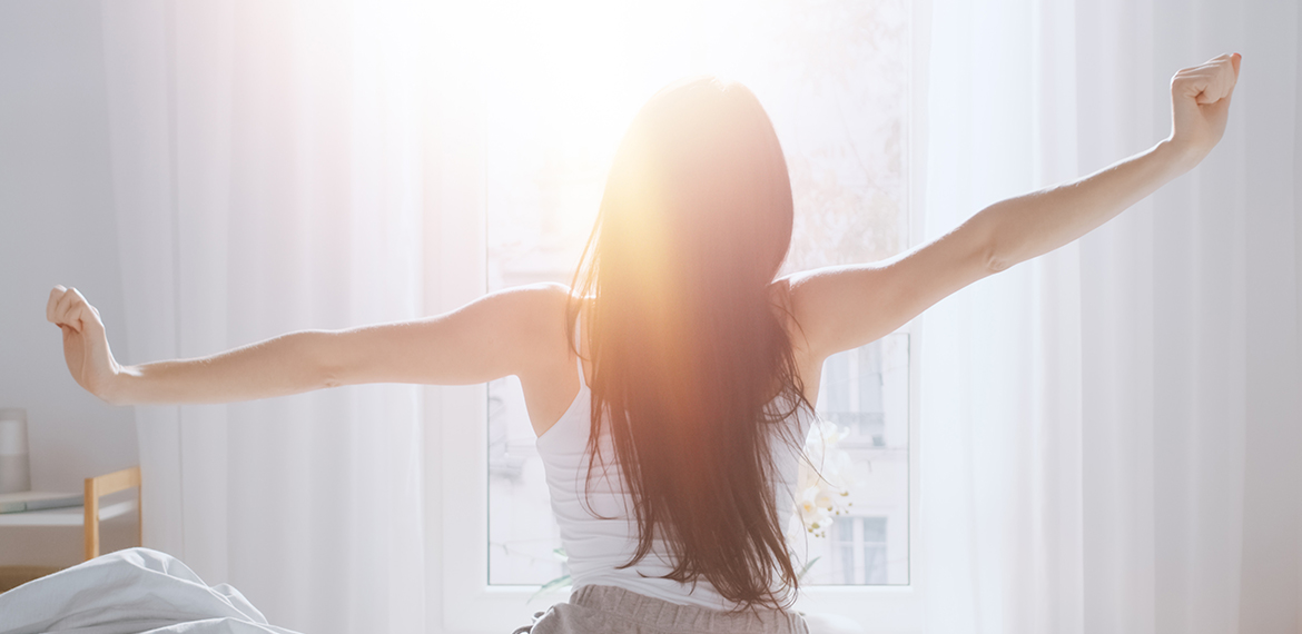 Woman stretching in the morning with relief after a good nights sleep